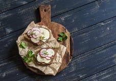 简单的健康早餐-乳酪萝卜和黑麦面包三明治在一个土气木切板 库存图片
