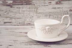 简单的土气白色陶器,空的盘 一杯大咖啡在前面天使的 木背景,破旧的别致,葡萄酒设色, 库存照片