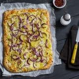 简单的土气酥脆饼用土豆、乳酪和红洋葱 免版税库存照片