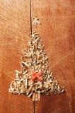 简单的圣诞树从锯木屑,在木背景的木片安排了 橙色逗人喜爱的丝带 免版税库存照片