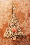 简单的圣诞树从锯木屑,在木背景的木片安排了 橙色逗人喜爱的丝带 库存照片