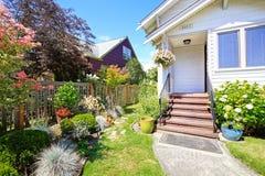 简单的房子外部 与台阶和花床的入口门廊 免版税库存图片