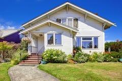 简单的房子外部 与台阶和花床的入口门廊 免版税库存照片