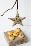简单的最低纲领派圣诞节装饰藤条星垂悬在一个干燥树枝的,在木箱子的椰子蛋白杏仁饼干,白色背景 库存图片