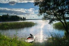 简单的渔夫`汽艇,被停泊对湖塞利格的岸边的森林在盲目的阳光下,俄罗斯 库存照片