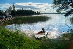 简单的渔夫`汽艇,被停泊对湖塞利格的空间的岸和看法在盲目的阳光下,俄罗斯 库存图片