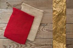 简单的织品礼物袋子,在简单的木背景的金黄丝带 库存照片