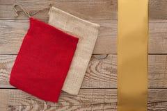 简单的织品礼物袋子,在简单的木背景的金黄丝带 图库摄影
