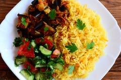 简单的菜意大利煨饭、被炖的茄子、沙拉用蕃茄和黄瓜在一块白色板材和一张木桌 库存照片