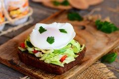 简单的菜沙拉和荷包蛋三明治 在黑麦面包切片的荷包蛋用在一个木板的新鲜蔬菜沙拉 库存照片