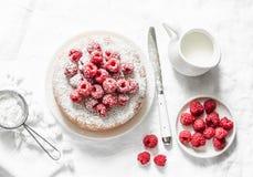 简单的蛋糕用搽粉的糖和新鲜的莓在轻的背景 夏天莓果点心 免版税库存图片