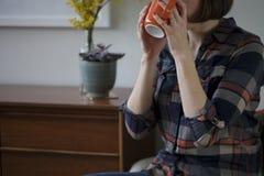 简单的衬衣的妇女喝从橙色杯子的 库存照片