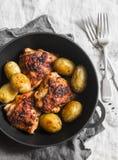 简单的被烘烤的鸡用在一个生铁平底锅的嫩土豆土豆在灰色背景,顶视图 免版税库存照片
