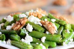 简单的青豆沙拉 青豆温暖沙拉用酸奶干酪、嘎吱咬嚼的核桃、大蒜和香料在板材 免版税图库摄影