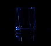简单的玻璃剪影在低调照明设备和表面反射的 库存照片