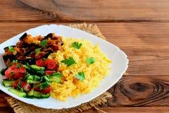 简单的素食者意大利煨饭,蕃茄和黄瓜沙拉,炖了在一块白色板材的茄子 与拷贝空间的布朗木背景 免版税库存图片