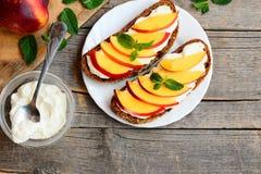 简单的黑麦三明治用软干酪和新油桃切片 在板材的明亮的夏天三明治 葡萄酒木背景 免版税库存图片
