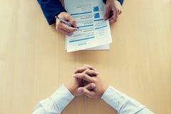 读简历的执行委员在工作面试和businessma期间 免版税图库摄影