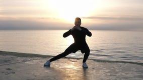 简而言之做准备在木地板上的肌肉,运动的高人在海附近 锻炼腿,舒展通过倾斜 股票录像
