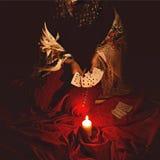 算命者通过打她的占卜用的纸牌在黑暗的灼烧的蜡烛在将来看见 免版税库存图片