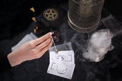 算命,占卜者投入占卜用的纸牌并且拼写摆锤 库存照片