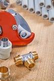 管子附件和切管机有管子的在木板 免版税库存图片