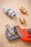 管子附件和可调扳手在木板 免版税库存照片