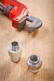 管子附件和活动扳手在木板 库存图片