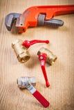 管子附件和活动扳手在木板 免版税库存照片