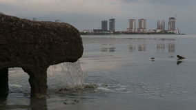 管子从污水系统的下水道水直接地在海附近在有摩天大楼的城市 股票视频
