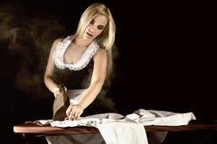 管家衣服的,有老铁的电烙的白色衬衣性感的白肤金发的妇女 在黑暗的背景的减速火箭的样式 免版税库存图片