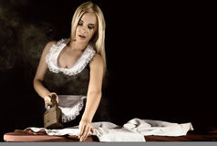 管家衣服的,有老铁的电烙的白色衬衣性感的白肤金发的妇女 在黑暗的背景的减速火箭的样式 免版税图库摄影