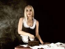管家衣服的,有老铁的电烙的白色衬衣性感的白肤金发的妇女 在黑暗的背景的减速火箭的样式 图库摄影