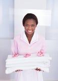 管家运载的毛巾在旅馆里 免版税库存图片