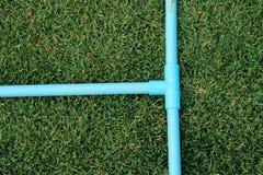 管接头,T插口PVC管,树方式蓝色pvc管子在绿色庭院里 图库摄影