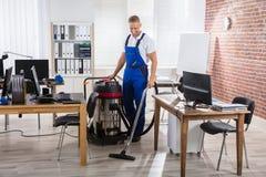 管理员与吸尘器的清洁地板 图库摄影