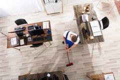 管理员与笤帚的清洁地板在办公室 免版税图库摄影