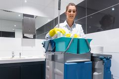 管理员或打杂的女佣人有她的看照相机在洗手间的工作工具的 库存照片