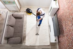 管理员有吸尘器的清洁地毯 免版税库存图片