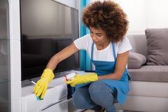 管理员有海绵的清洁家具 免版税图库摄影
