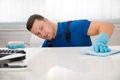 管理员有海绵的清洁书桌在办公室 免版税库存图片