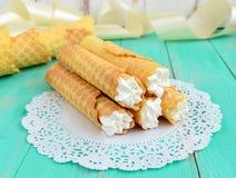 以管的形式嫩蜂蜜薄酥饼,充塞用在白色鞋带餐巾的空气奶油 库存图片