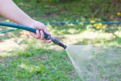 从水管的运作的浇灌的庭院 库存照片