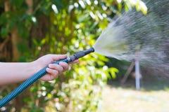 从水管的运作的浇灌的庭院 图库摄影