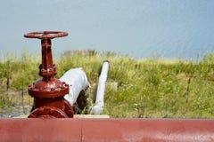 管道的停机阀以一个人工湖为背景的 库存图片