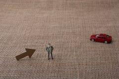箭头和人小雕象和一辆红色玩具汽车 免版税库存照片