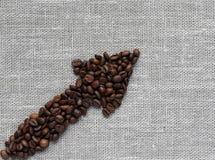 箭头由咖啡豆制成在一种亚麻制织品 免版税库存照片