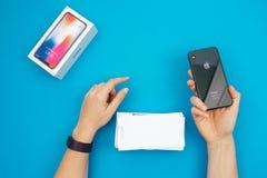 箱中取出一个新的苹果计算机Iphone x旗舰智能手机 免版税库存图片