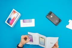 箱中取出一个新的苹果计算机Iphone x旗舰智能手机 免版税图库摄影