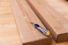 箱中取出纸板箱有建筑刀子的新的家具 搬到新房,新的家具购买  图库摄影